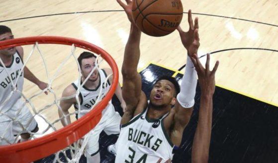 Milwaukee Bucks forward Giannis Antetokounmpo (34) reaches for the ball during the first half against the Phoenix Suns in Game 5 of basketball's NBA Finals on Saturday in Phoenix.