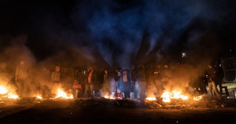 Armed community members gather around a fire to keep warm at a roadblock set up in Phoenix Township, North Durban, on Thursday to prevent looters from reaching the community.