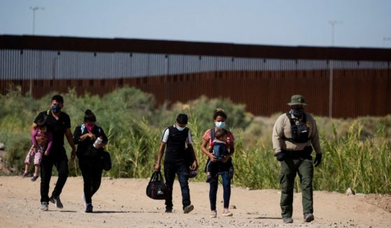 Migrants from Guatemala follow an officer after illegally crossing the border between the United States and Mexico into Yuma, Arizona, on May 12.