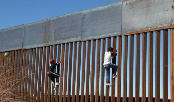 People climb the border wall between Mexico and the U.S. in Ciudad Juarez, Mexico, on Jan. 26, 2017.