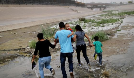 Migrants hold hands as they cross the border between the U.S. and Mexico at the Rio Grande river, on their way to enter El Paso, Texas, on May 20, 2019.