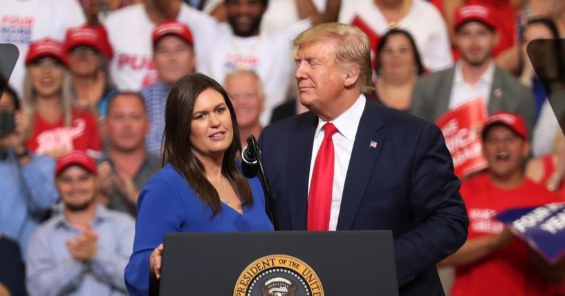 Then-President Donald Trump stands with Sarah Huckabee Sanders at the Amway Center on June 18, 2019, in Orlando, Florida.