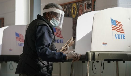 A poll worker cleans a voting booth between voters as residents of Baltimore City cast their votes in the U.S. presidential and local congressional elections at Western High School on Nov. 3, 2020, in Baltimore.