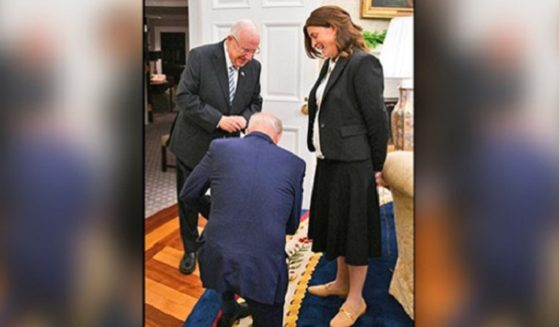 President Joe Biden kneels in the Oval Office as a tribute to an aide to outgoing Israeli President Reuven Rivlin.