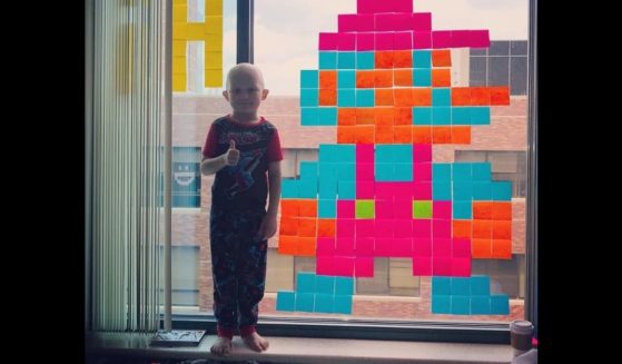 Meyer Mixdorf, 5, stands with one of the pieces he and his family made in a friendly battle of post-it note art that began during a stay at a hospital while he was treated for cancer.