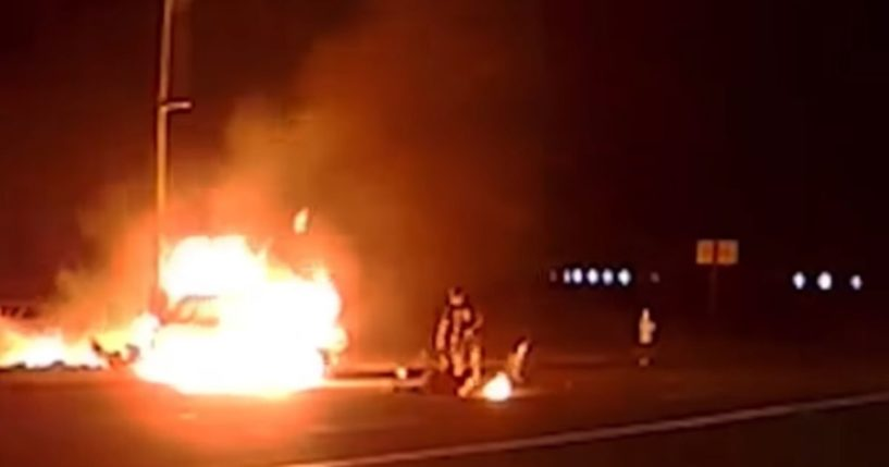 Officer Mark Afanasev attends to two people involved in a fiery accident.