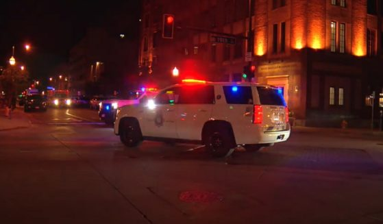 A police vehicle with flashing lights sits outside the Maven Hotel in Denver during a weapons raid.