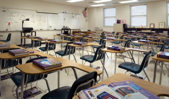 An empty classroom is seen in the stock image above.