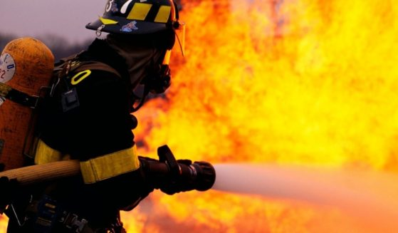 A firefighter sprays water at a fire in this stock image.