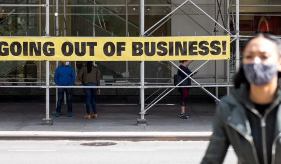 """A woman wearing a mask walks by a """"going out of business"""" sign on Sept. 20, 2020, in New York City."""