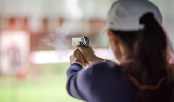 A woman fires a gun in the above stock image.