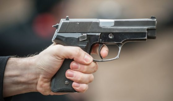 A man aims a gun in the above stock image.