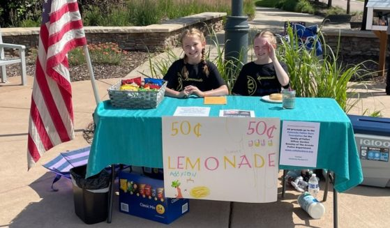 Scarlet and Addyson with the lemonade stan they ran to help raise funds for a fallen officer.
