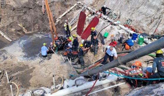 Firefighters work to free a man trapped in a sinkhole at a construction site in Florida.