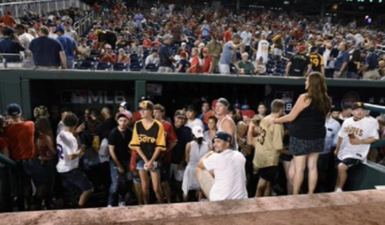 Fans gather in a dugout Saturday after a game at Nationals Park in Washington was halted by an incident of gunfire outside the stadium.