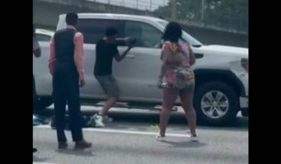 Strangers on an interstate in Atlanta attempt to break into a man's truck to help him.