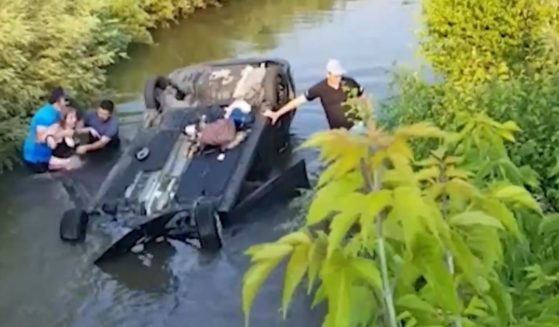 The flipped and submerged car that Rob Reynolds helped a driver escape from.