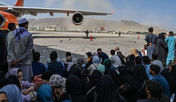 Afghan people sit as they wait to leave the Kabul airport