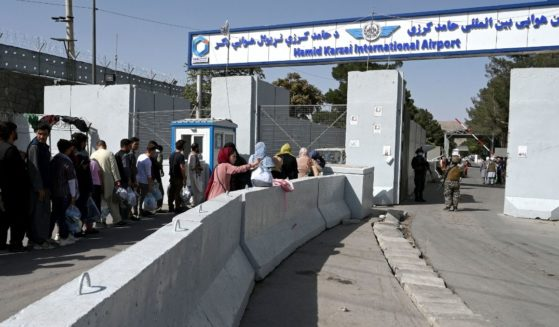 Afghans line up at the main entrance gate of the Kabul airport on Saturday in Afghanistan.