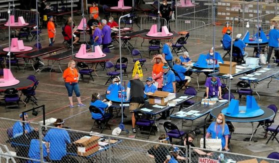 Maricopa County ballots cast in the 2020 general election are examined and recounted by contractors working for the Florida-based company Cyber Ninjas at Veterans Memorial Coliseum in Phoenix on May 6, 2021.