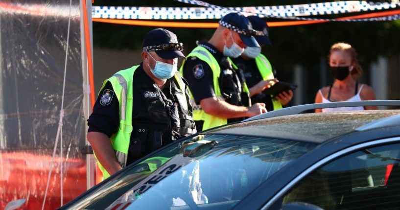 Queensland Police stop cars at the state's border on Wednesday in Coolangatta, Australia, to check drivers' vaccination status.