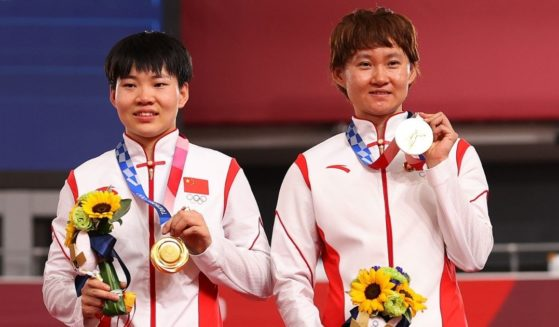 Bao Shanju and Zhong Tianshi of China pose with their gold medals after winning the women's team sprint track cycling finals at the Tokyo Olympics at Izu Velodrome on Monday in Izu, Shizuoka, Japan.
