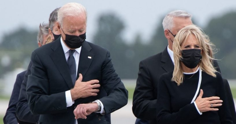 President Joe Biden appears to look down at his watch while standing alongside first lady Jill Biden during the dignified transfer of the remains of fallen service members at Dover Air Force Base in Delaware on Sunday.