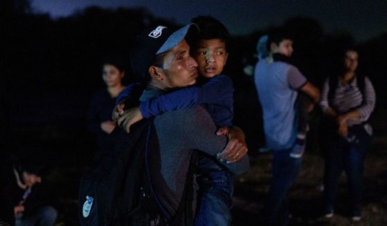 Honduran Eric Villanueva, left, holds his son Eric, 7, while waiting to be led to a United States Border Patrol processing area after crossing the U.S.-Mexico border on a raft into the United States in Roma, Texas, late on July 9, 2021.
