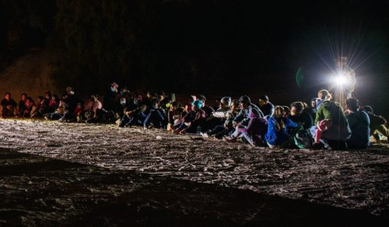 Immigrants wait to be accounted for and taken to a Border Patrol processing facility after crossing the Rio Grande into the U.S. on June 18, 2021, in Roma, Texas.