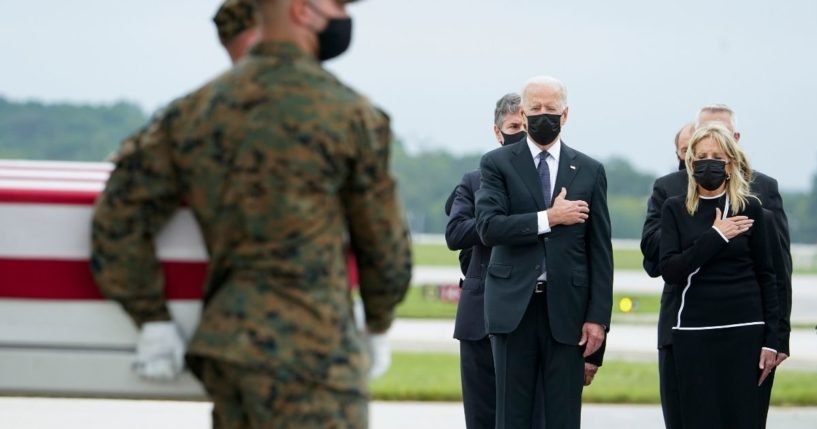 President Joe Biden and first lady Jill Biden watch as a Marine Corps carry team moves a transfer case containing the remains of Marine Corps Sgt. Johanny Rosario Pichardo, 25, of Lawrence, Massachusetts, on Sunday at Dover Air Force Base, Delaware.