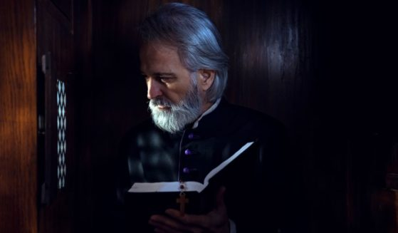 This stock image portrays a Catholic priest sitting in a confession booth. The Catholic Church has removed a conservative priest from ministry seemingly due to his comments asserting that Catholic priests cannot be members of the Democratic Party.