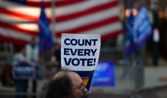 """A man holds a placard that reads """"Count Every Vote"""" while demonstrating across the street from supporters of President Donald Trump outside of where votes are being counted on Nov. 9, 2020 in Philadelphia, Pennsylvania."""