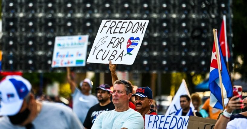 People hold freedom signs during a rally in Miami calling for freedom in Cuba, Venezuela and Nicaragua on Saturday.