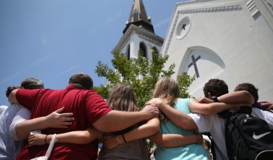 People pray in front of Emanuel African Methodist Episcopal Church on the one-month anniversary of a mass shooting there on July 17, 2015, in Charleston, South Carolina.