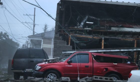 Vehicles are damaged after the front of a building collapsed during Hurricane Ida on Sunday in New Orleans.