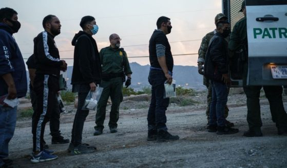 Migrants caught crossing the U.S.-Mexico border are loaded into a transport van by U.S. Border Patrol agents in Sunland Park, New Mexico, on July 22, 2021.