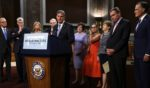 Democratic Sen. Joe Manchin of West Virginia speaks about the bipartisan infrastructure package while his fellow negotiators -- from left, Sens. Kevin Cramer of North Dakota, Bill Cassidy of Louisiana, Lisa Murkowski of Alaska, Rob Portman of Ohio, Susan Collins of Maine, Kyrsten Sinema of Arizona, Jeanne Shaheen of New Hampshire, Mark Warner of Virginia and Mitt Romney of Utah -- listen during a news conference at the Dirksen Senate Office Building on Capitol Hill in Washington on July 28.