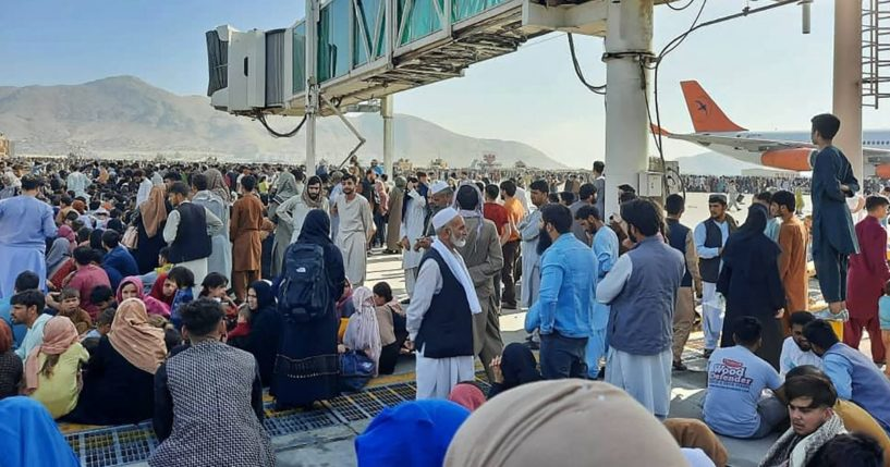 People crowd the tarmac of the Kabul airport on Monday to flee the country as the Taliban takes control of Afghanistan.