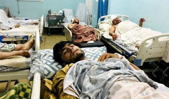 Wounded Afghans lie on a bed at a hospital after a deadly explosions outside the airport in Kabul, Afghanistan, on Thursday.