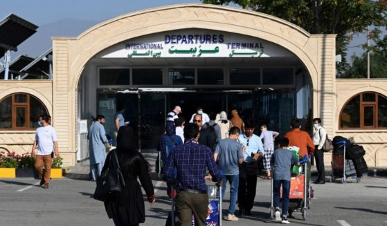 Passengers queue to enter the departures terminal of Hamid Karzai International Airport in Kabul on July 17, 2021.