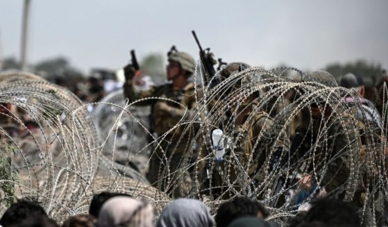 A U.S. soldier shoots in the air with his pistol while standing guard behind barbed wire as Afghans sit on a roadside near the military part of the airport in Kabul on August 20, 2021.