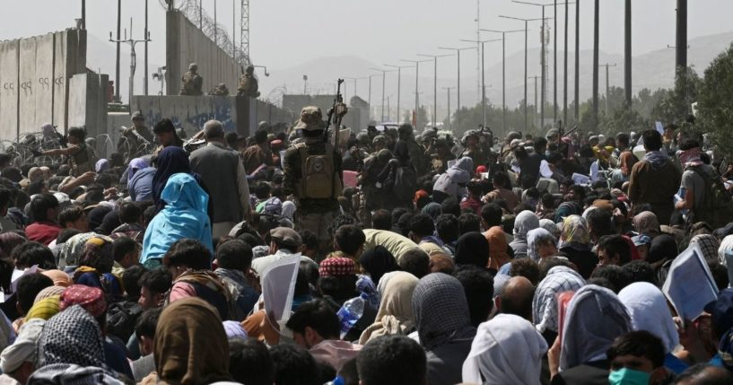 Afghans gather on a roadside near the military part of the airport in Kabul on Friday, hoping to flee from the country after the Taliban's military takeover.