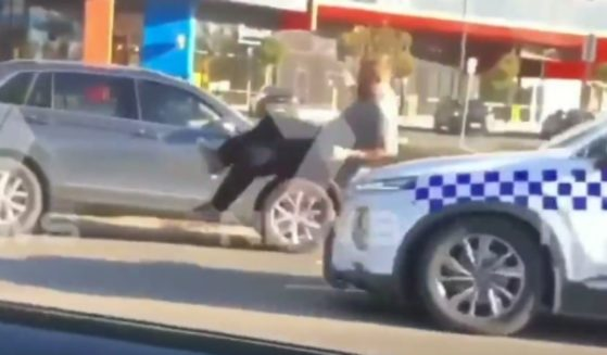 A man is hit by a police car during an altercation in Australia, as shown in a video posted on Sunday.