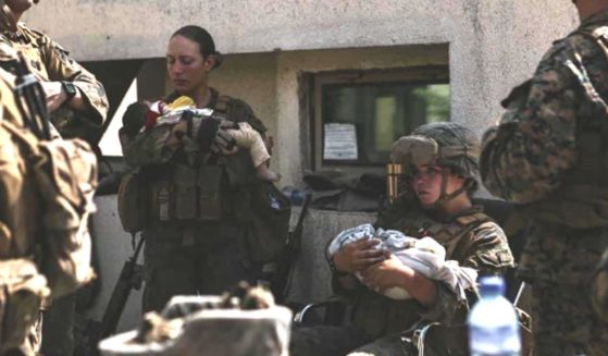 U.S. Marine Sgt. Nicole Gee, left, holds a baby while assisting with the evacuation effort in Kabul, Afghanistan. Gee was killed in a suicide bombing on Thursday.