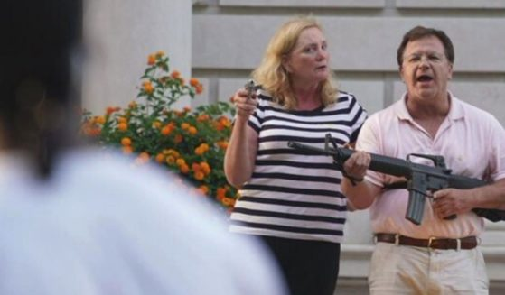 Mark and Patricia McCloskey of St. Louis hold firearms as demonstrators approach their home.