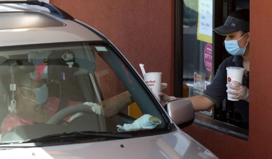 A McDonald's worker wears a mask and gloves as she hands soft drinks to a customer at a drive-thru in Novato, California, on April 22, 2020.