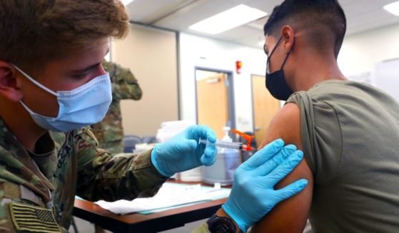 Army Spc. Tyler Boyer administers the COVID-19 vaccine to another soldier at Fort Carson, Colorado, on Tuesday.