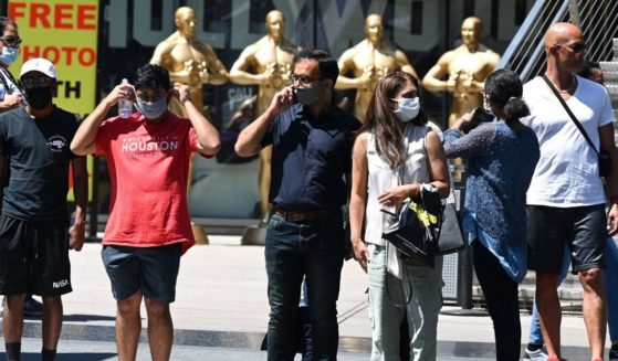 People wearing masks wait to cross the street in Hollywood, California, on July 19, 2021.