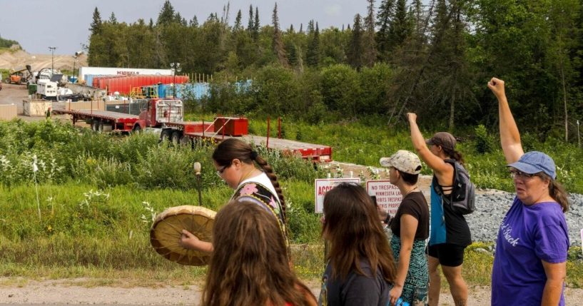 Activists raise their fists as they pass sections of the Enbridge Line 3 pipeline construction during the 'Treaty People Walk for Water' event near the La Salle Lake State Park in Solway, Minnesota, on Saturday.
