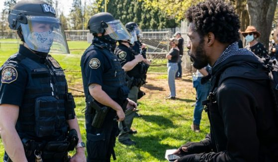 A protester yells at a Portland, Oregon, officer after a fatal police shooting in the city's Lents Park on April 16.